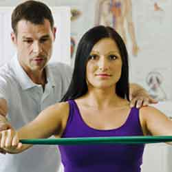 Man helping a woman with physiotherapy services.